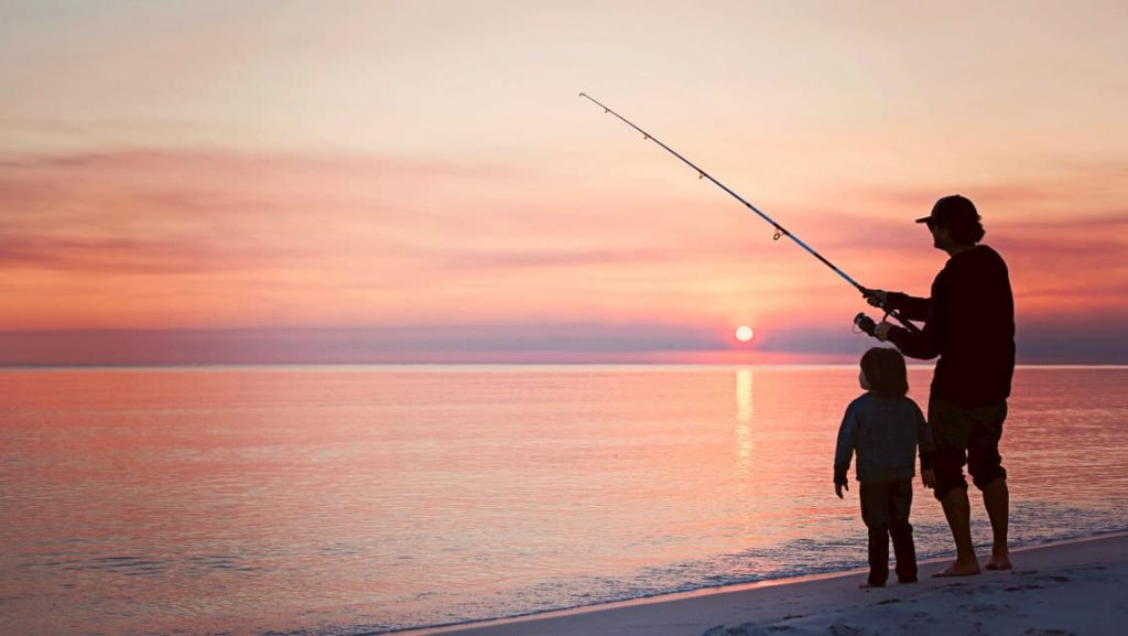Angler surf fishing with his son using a spinning fishing rod