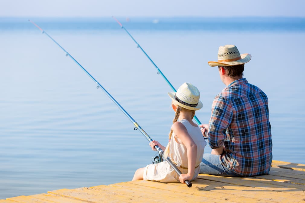 Father and daughter sitting on dock fishing.