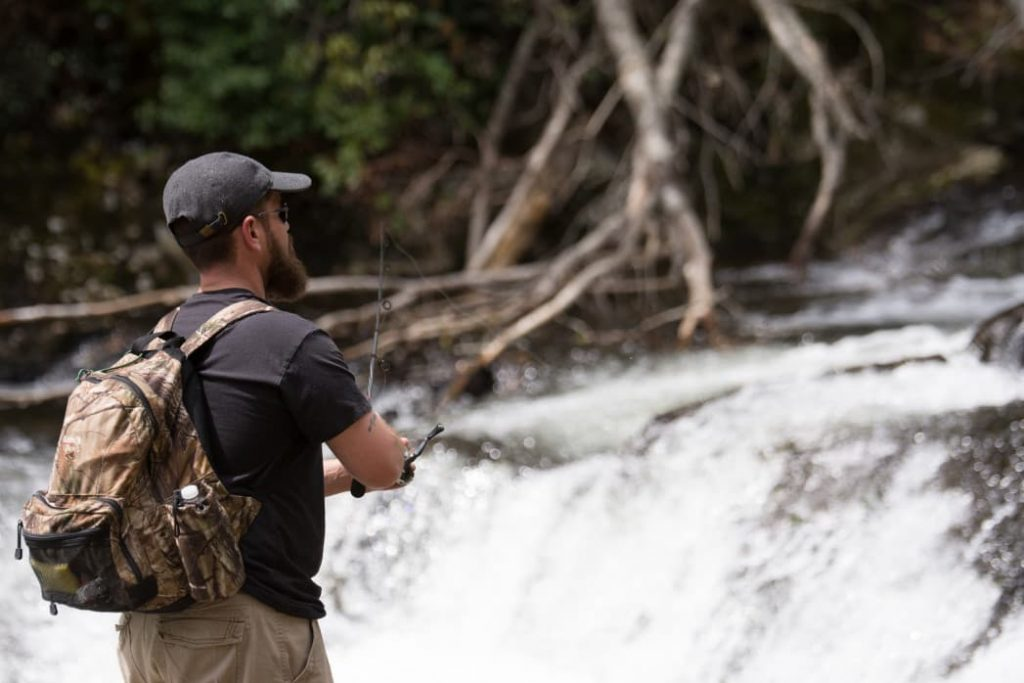 Man fishing in a river while wearing a backpack